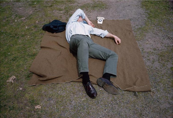 Man asleep on blanket with tiny telephone, New Jersey (1965) by Joel Meyerowitz at